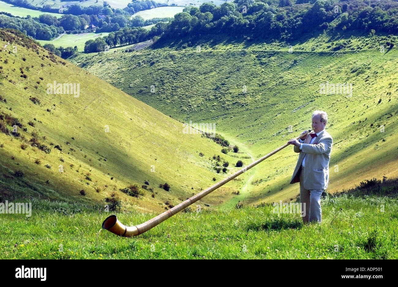 Man playing an Alpenhorn or alphorn the strange Swiss musical instrument on the 'South Downs' 'National Park' - Stock Image