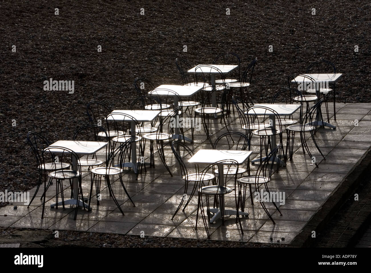 Deserted tables and chairs out of season on Brighton beach South Coast England United Kingdom - Stock Image