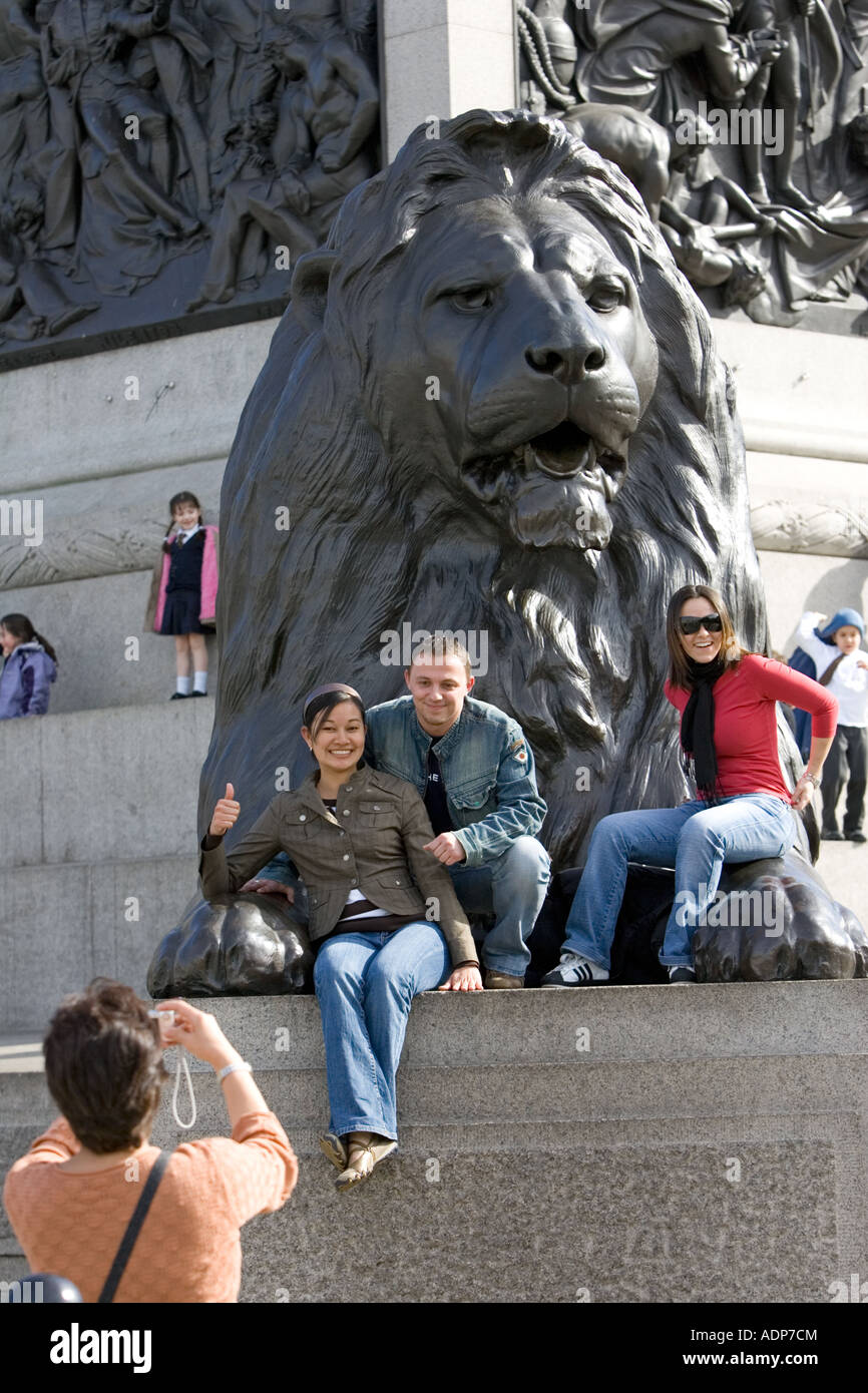 Tourists pose for photographs on lion statue at base of Nelson s Column Trafalgar Square London UK - Stock Image