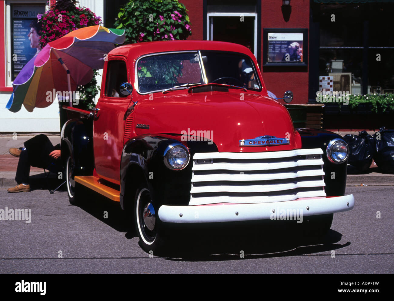 An Old Shiny Red And Black Chevrolet Truck With A Brightly Coloured