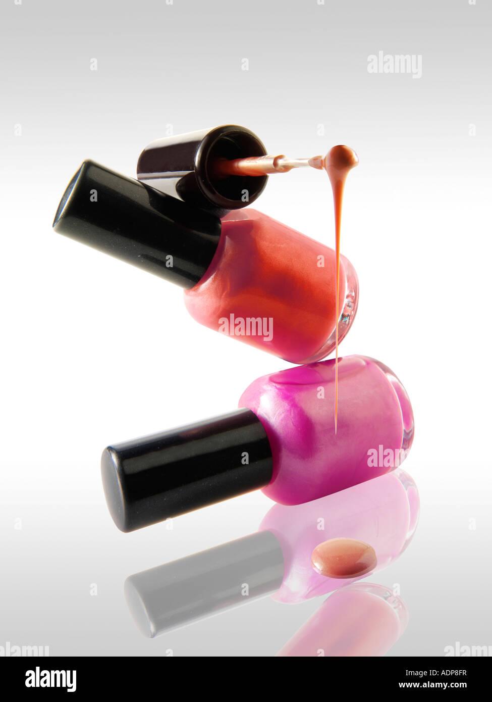 2 Nail Polish bottles balanced on each other in a fun way with a nail varnish brush balanced ontop dripping nail - Stock Image
