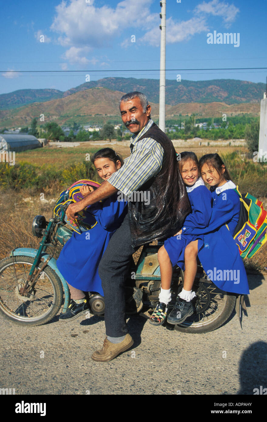 Father and daughters on moped in Fethiye on the Turquoise Coast of Mediterranean Turkey - Stock Image