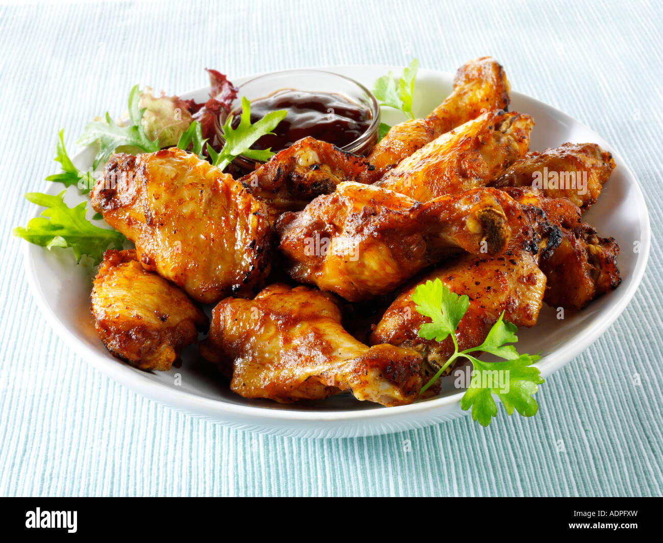 Bowl of spicy BBQ Chicken wings and thights - Stock Image