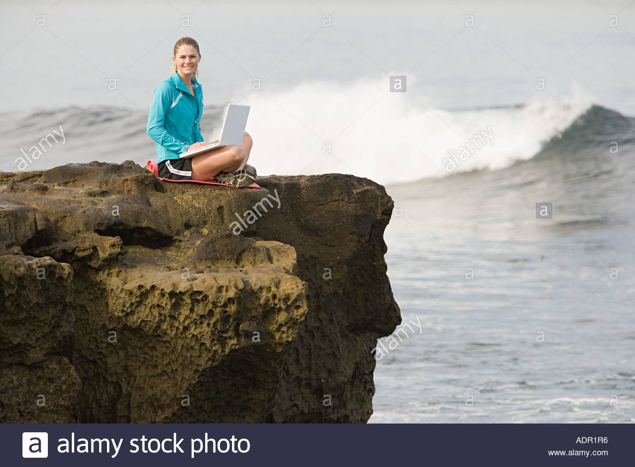 Woman using laptop by the ocean - Stock Image