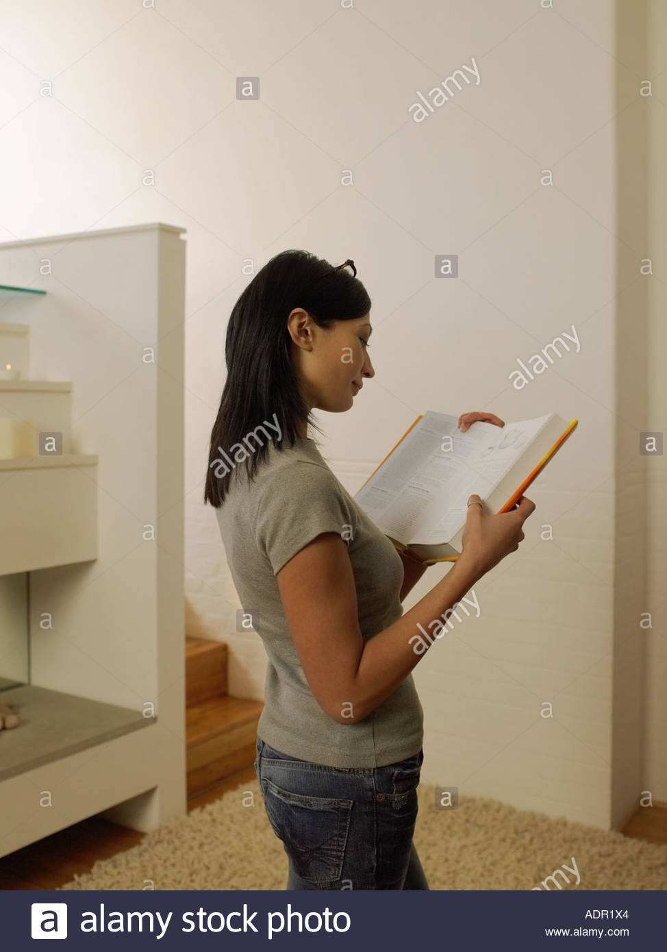Woman reading a reference book - Stock Image