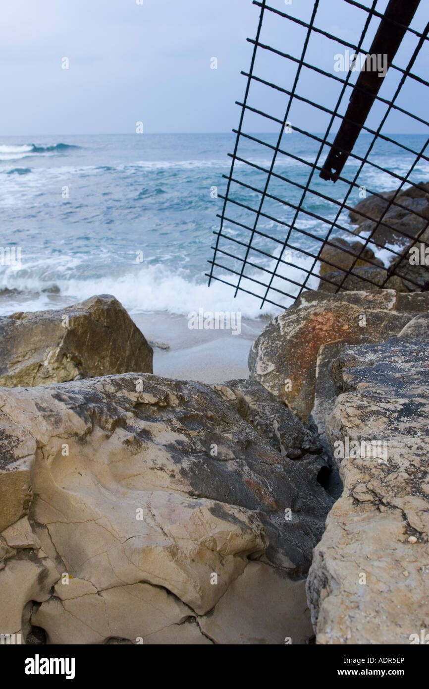 Stock Photo of Rocks and Fallen Fence at Beach Displaying Environmental Neglect - Stock Image