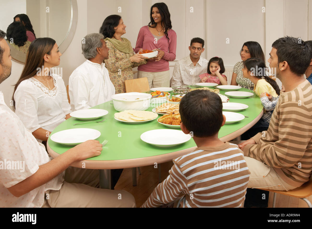 Large family at dining table - Stock Image