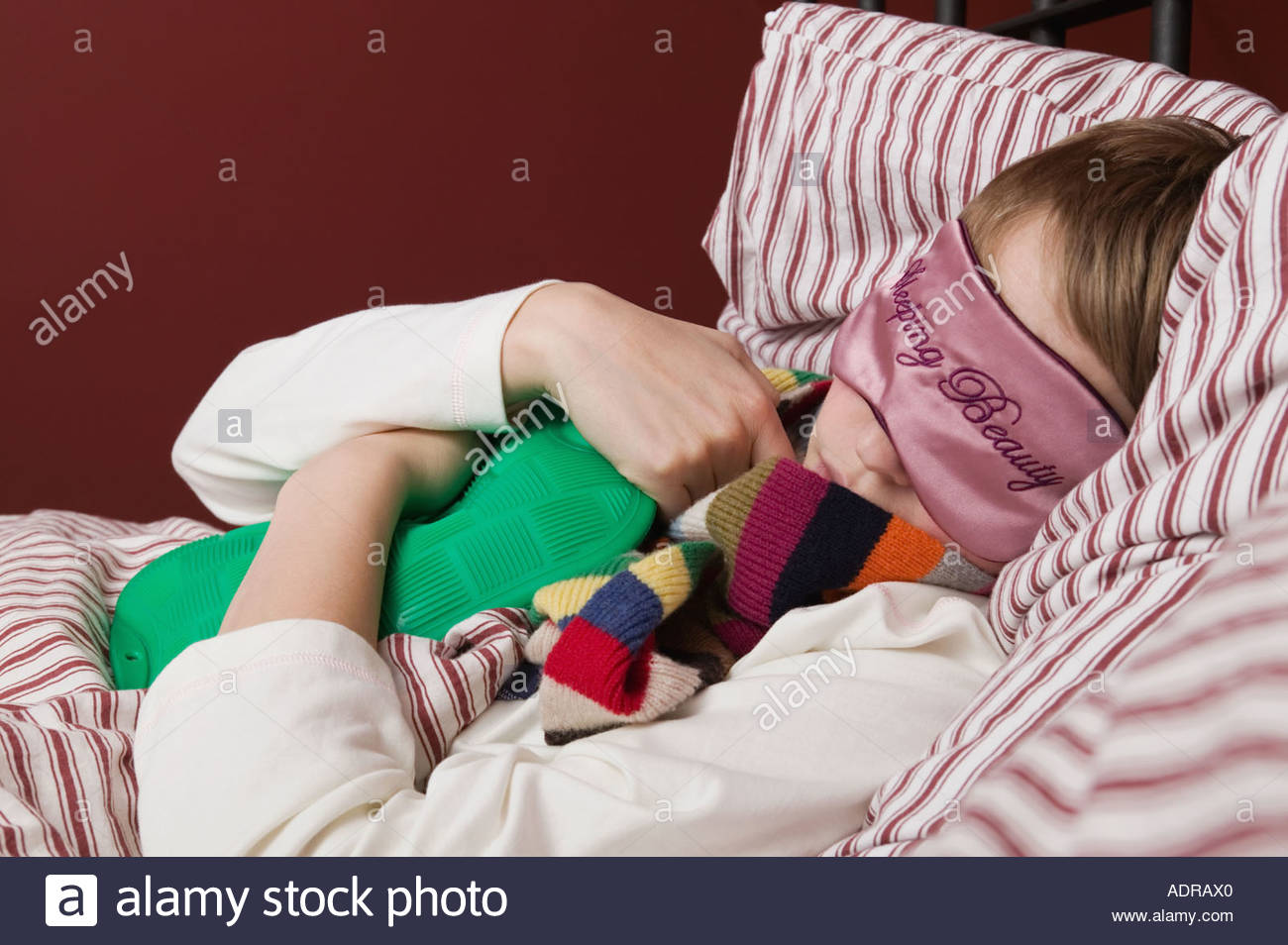 Girl sleeping with a hot water bottle - Stock Image