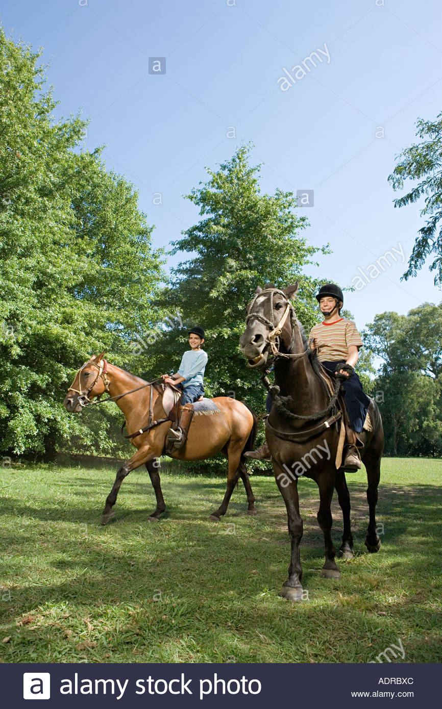 Brother and sister horseback riding - Stock Image