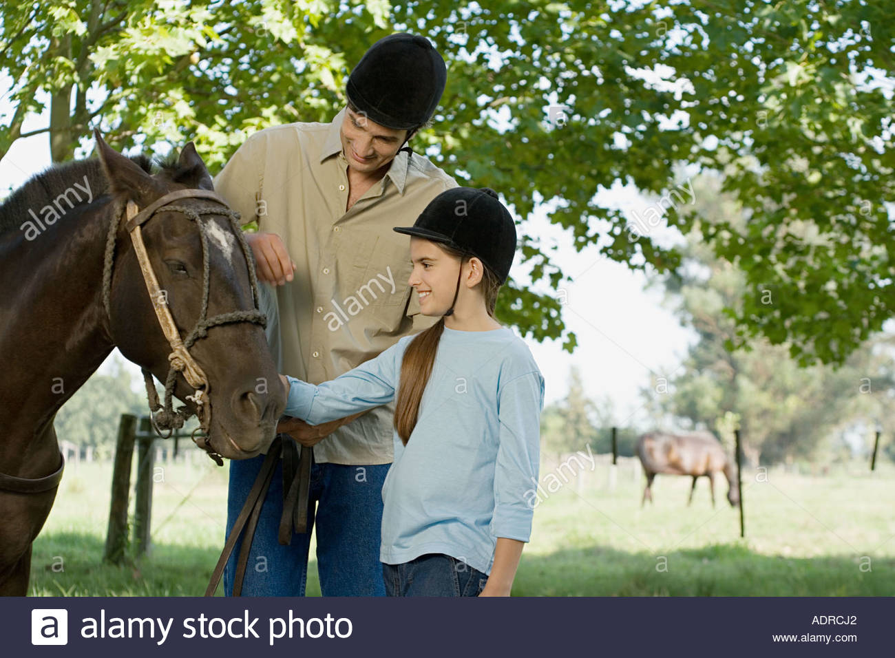Father and daughter horseback riding - Stock Image
