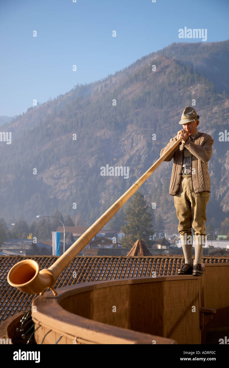 Man in Bavarian clothing playing Alpine Horn on balcony ledge at Enzian Hotel in Leavenworth Washington - Stock Image