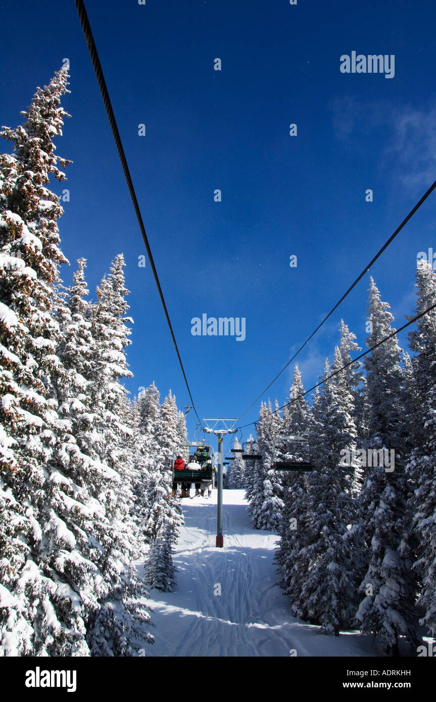 USA Colorado Vail Ski Resort Skiers being carried on a chair lift in Vail back bowls - Stock Image