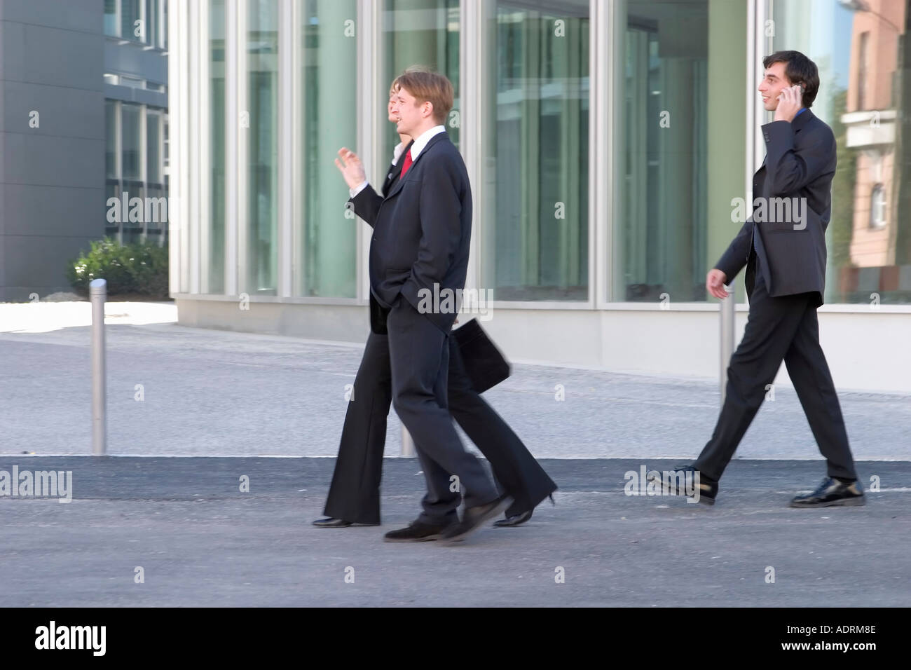 3af3f62ea1ca Man and woman in business clothing converse. ADRM99 (RF). 3 three  businessmen strolling while lunch break in front of business building -  Stock Image