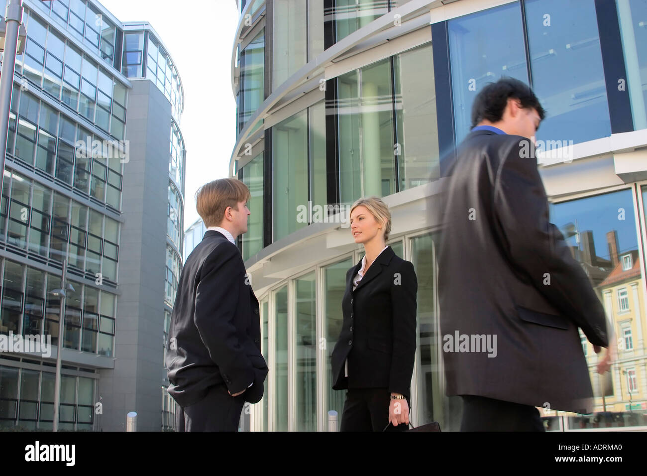 73a095b57ab3 Man and woman in business clothing converse while another businessman  passes by