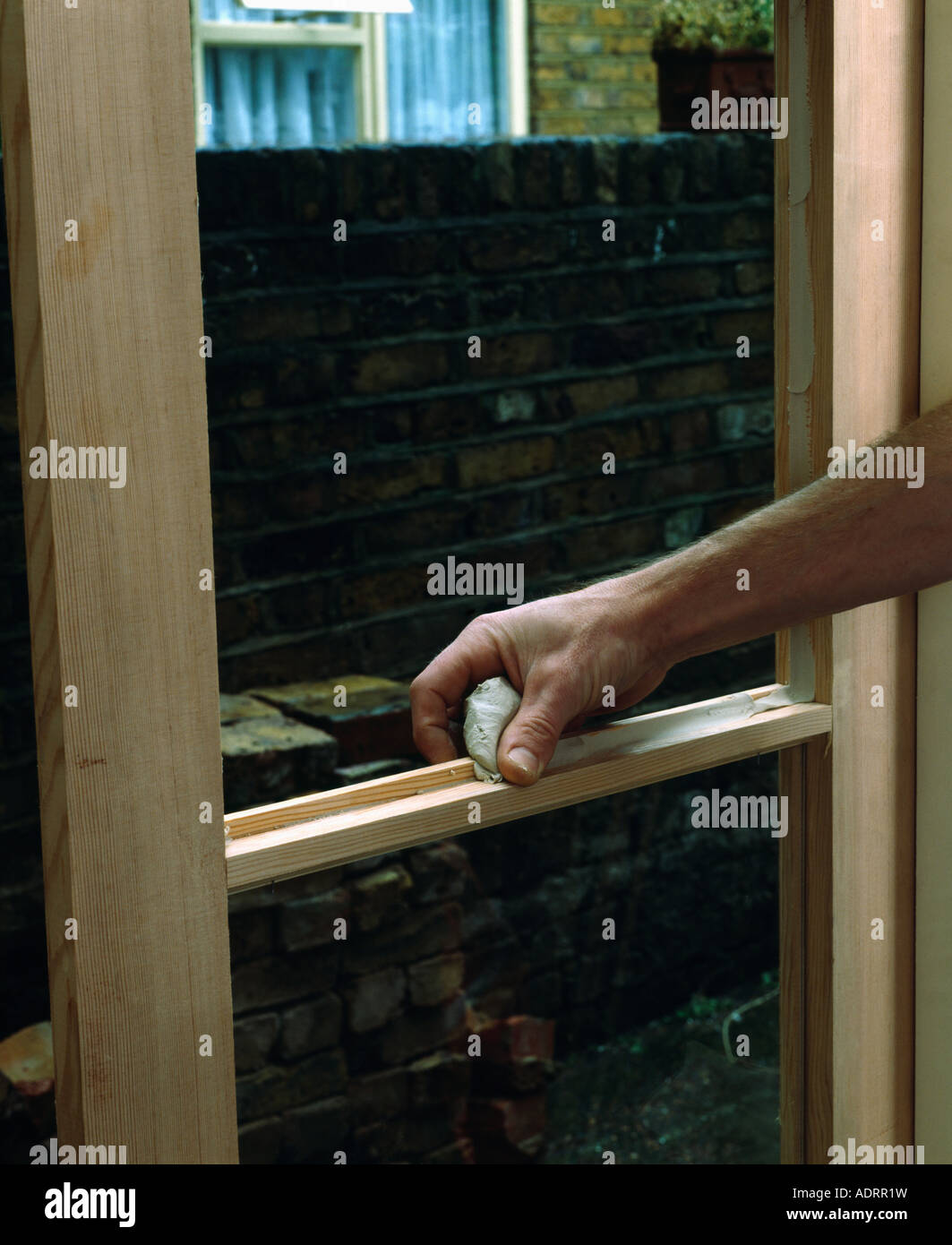 Close up of hands applying putty to new wooden window-frame Stock ...