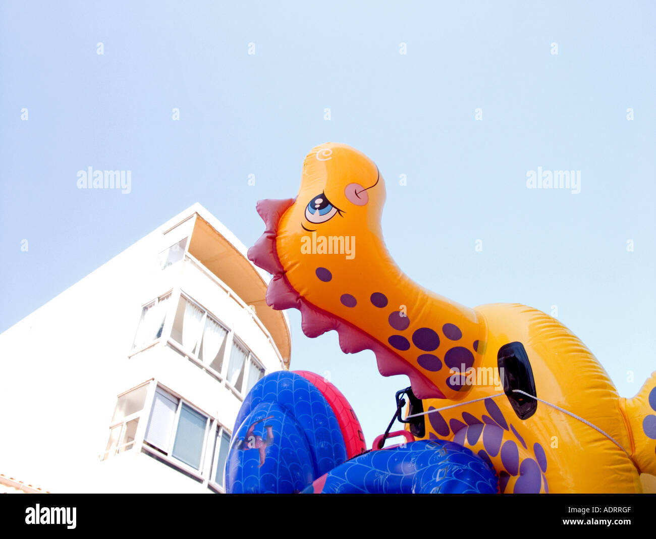 an inflatable toy yellow and orange dragon looks skywards   with flats in background - Stock Image
