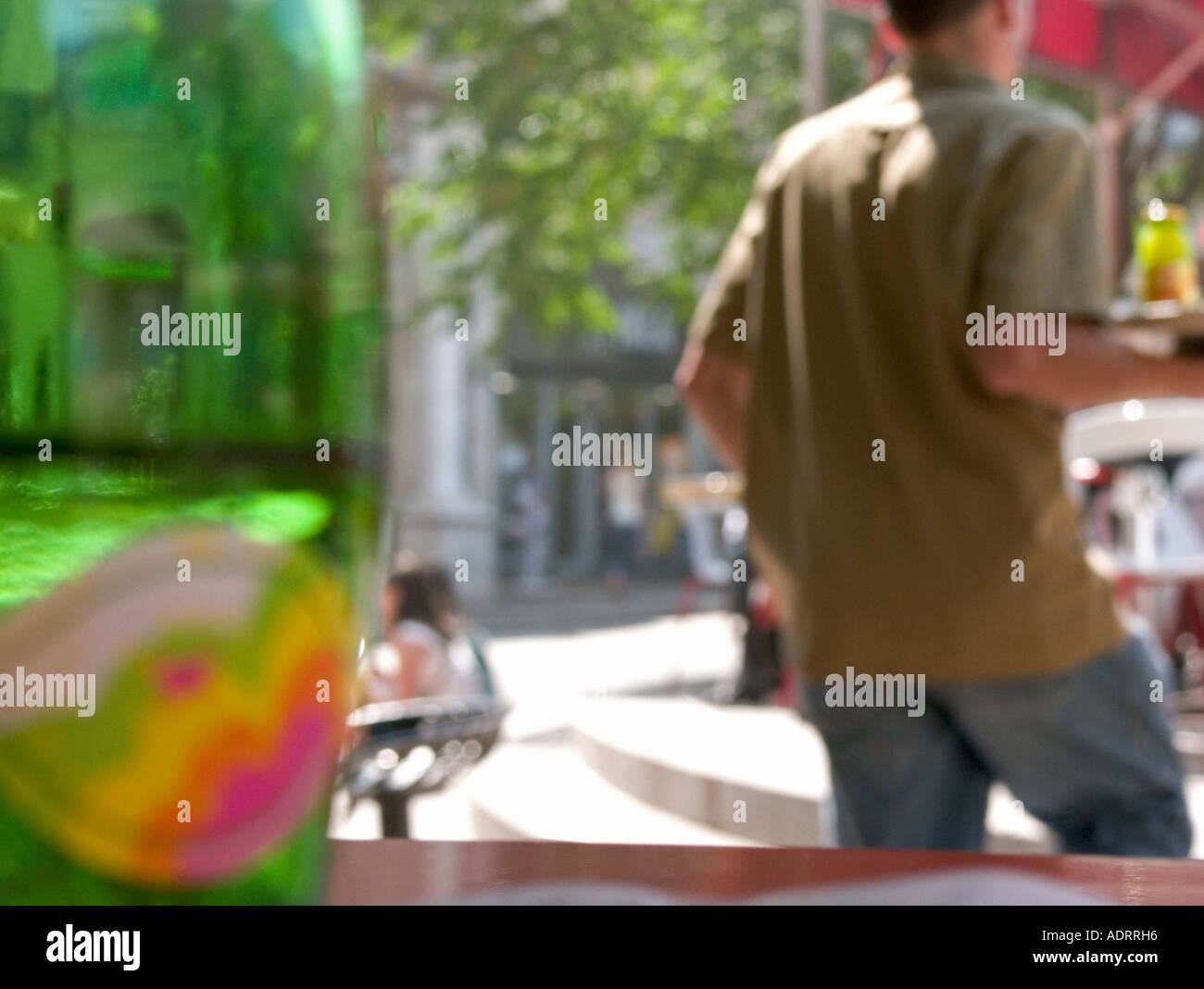 a blurred view of a french waiter carrying a tray of drinks - Stock Image