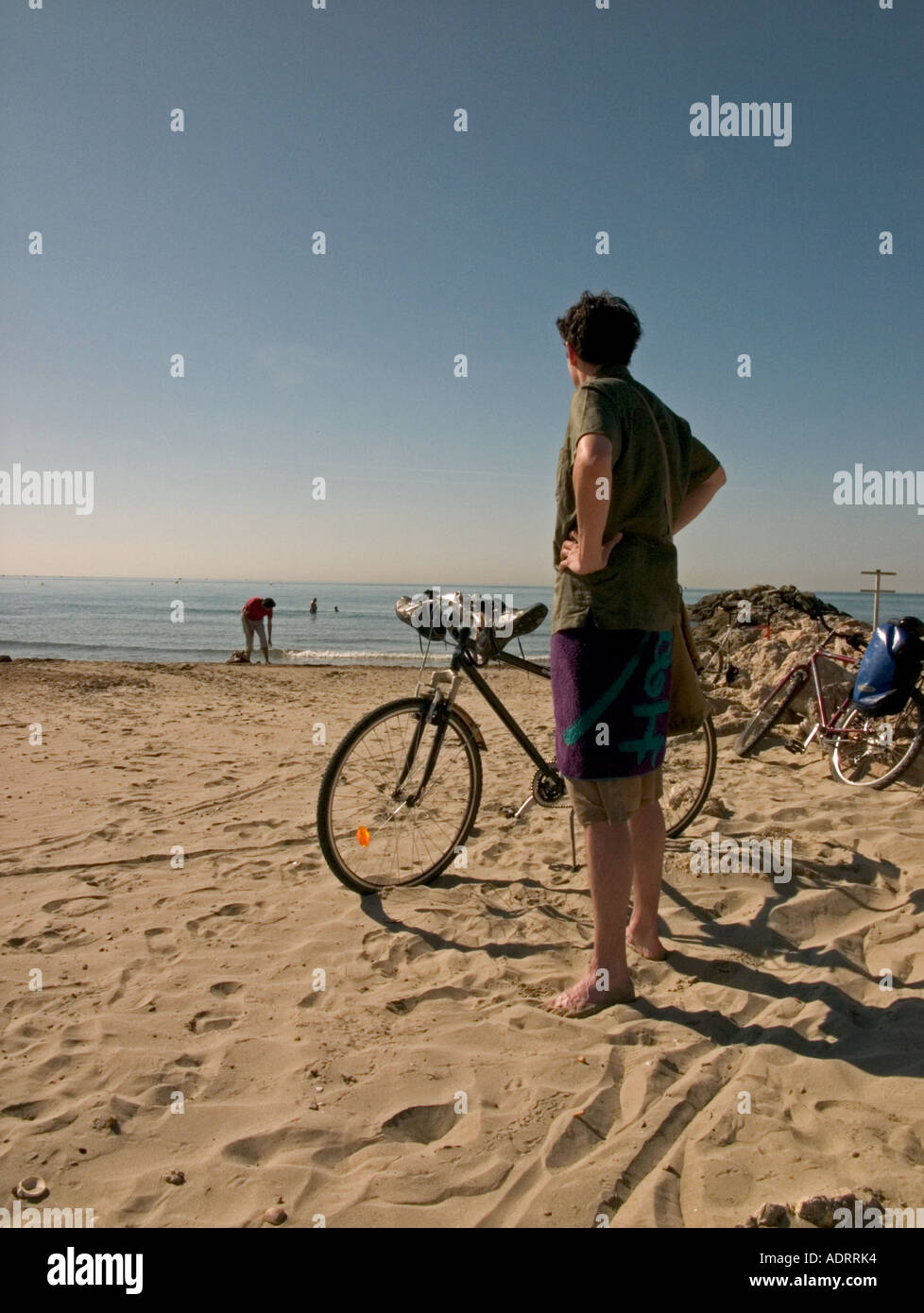 a young man waits by his bike on a beach with hands on hips - Stock Image