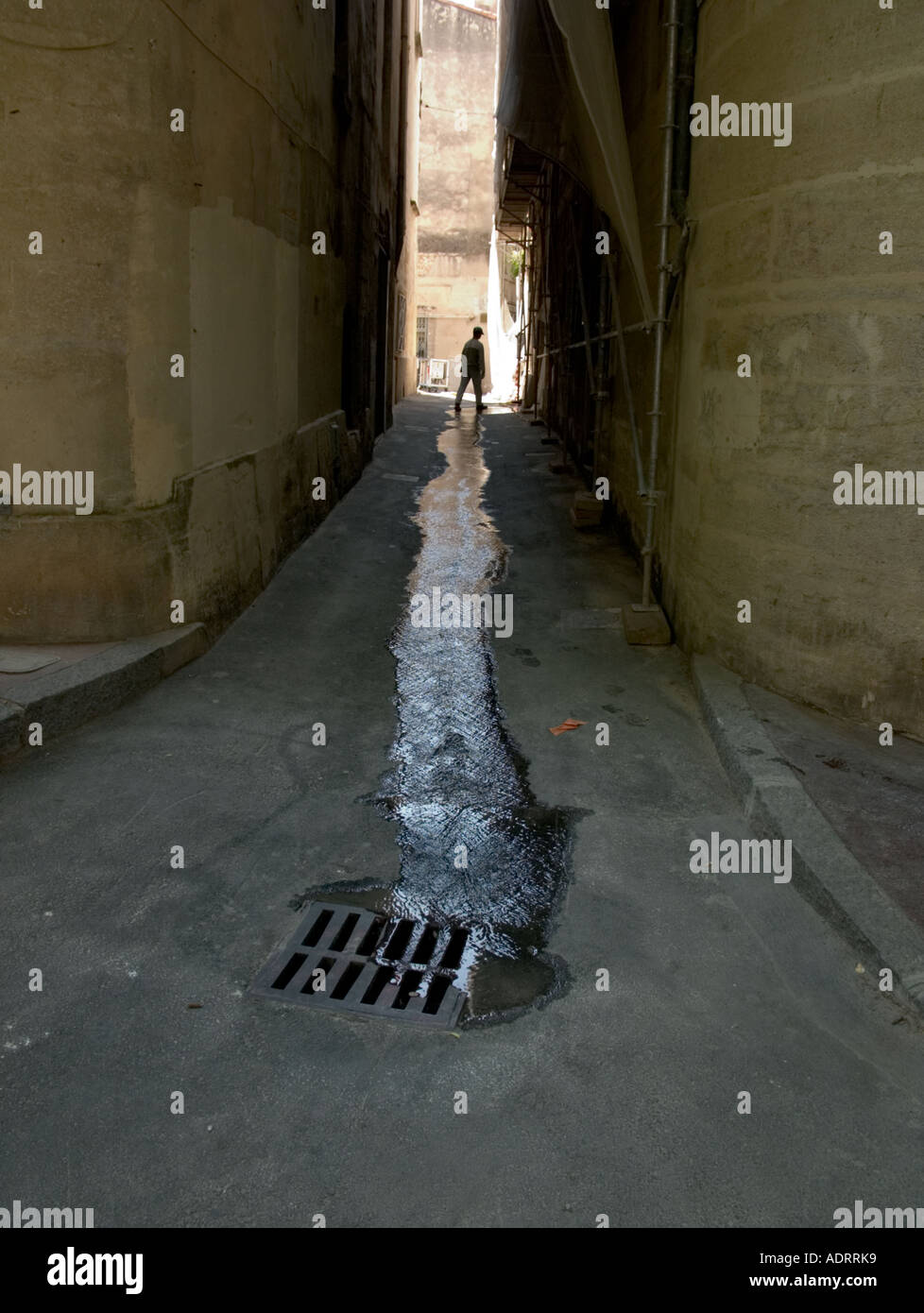 A lone man walks though a water leak in a dark alleyway - Stock Image