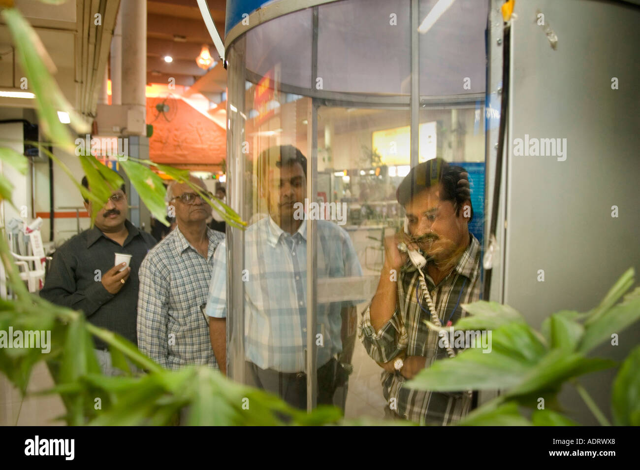 People queue to use a public call box at Poona airport that uses a mobile phone technology GSM India - Stock Image