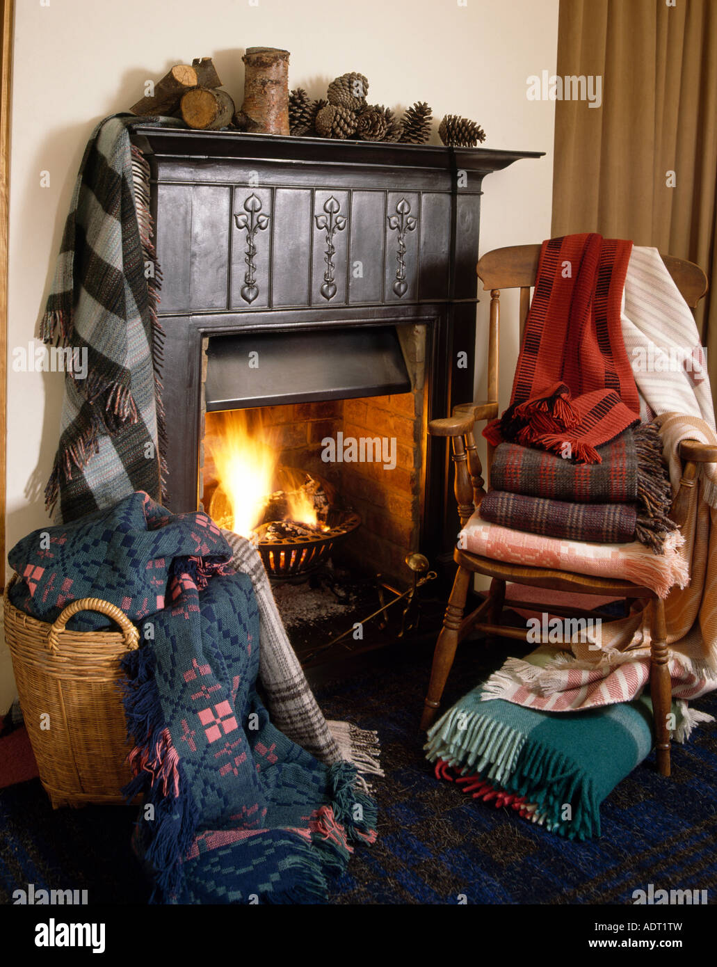 Welsh Blankets In Large Basket Beside Fireplace And Pile Of Blankets