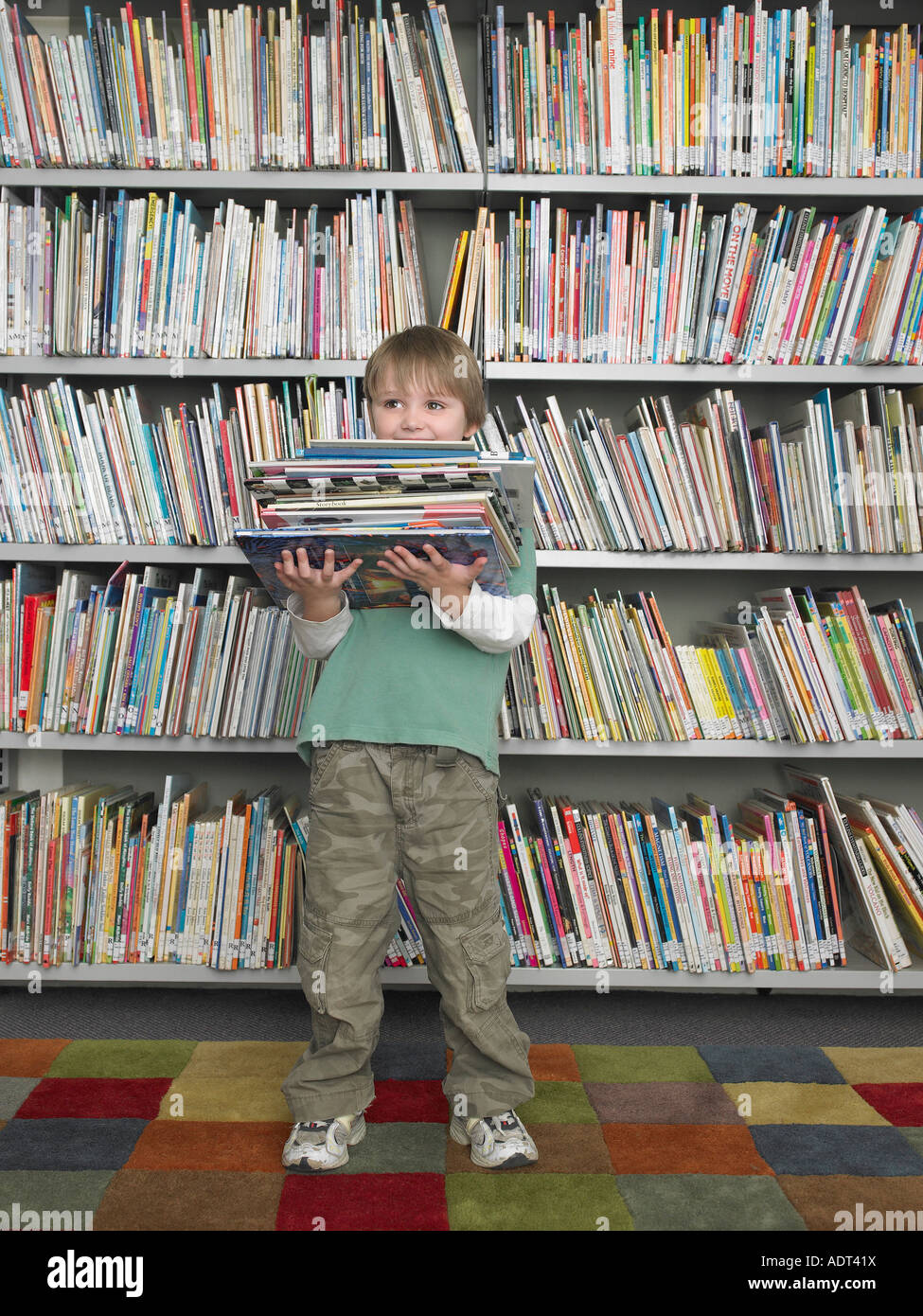 Boy Holding Stack Of Books In Front Library Bookshelf