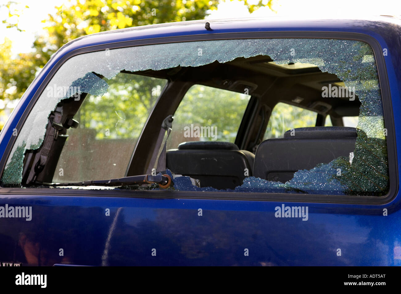 broken rear window of blue renault car smashed by vandals - Stock Image