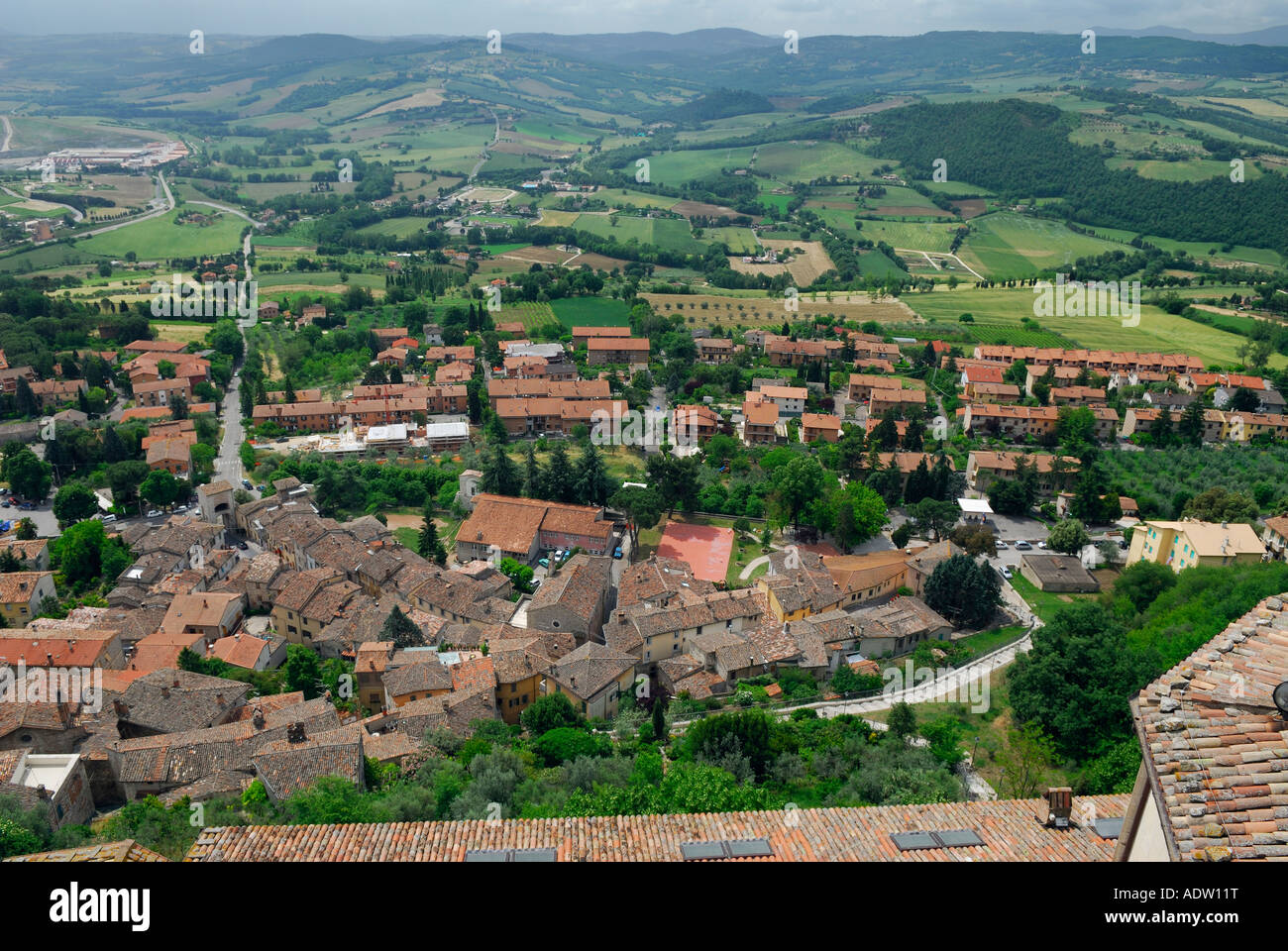 Vista of rooftops and green pastureland withTiber valley hills and Mount Martani from San Fortunato church in Todi - Stock Image