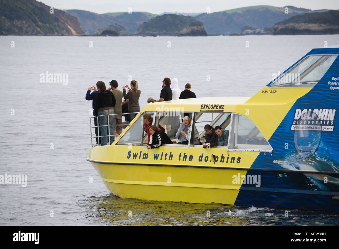 Tourist group taking photographs on dolphin watching catamaran cruise boat Bay of Islands Northland North Island - Stock Image