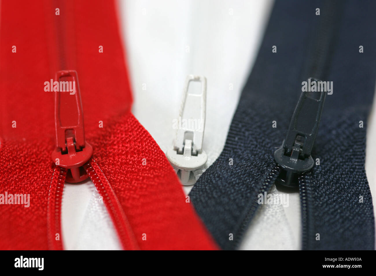Red white and blue zips with limited depth of field and selective focus on a white background - Stock Image