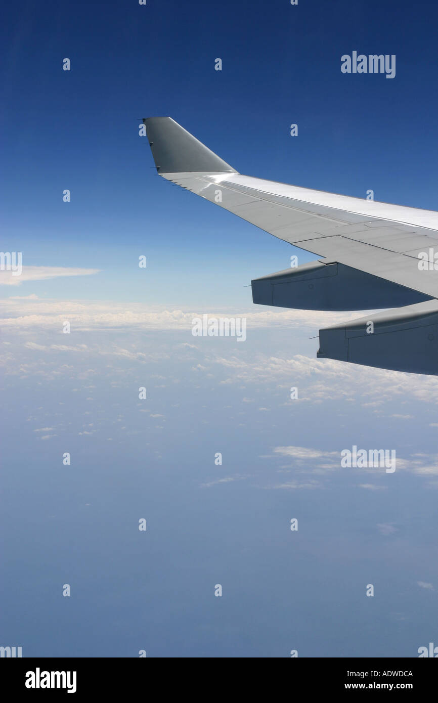 View of a commercial airliner wing through the window of a passenger plane with bright blue sky and fluffy white clouds - Stock Image