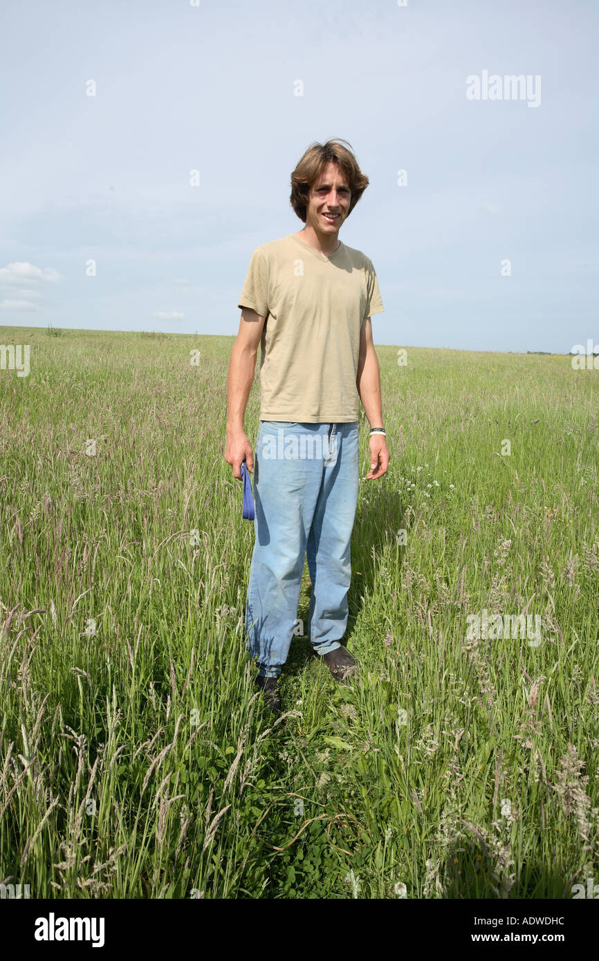 Young farmer early twenties in a field of grass Hampshire England. - Stock Image