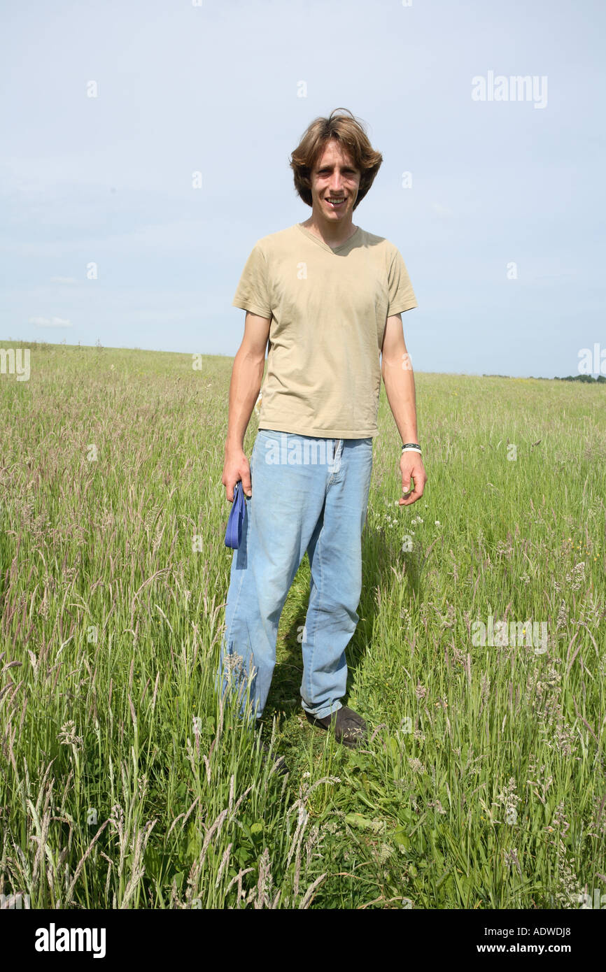 Young farmer early twenties in a field of wheat, Hampshire England. - Stock Image