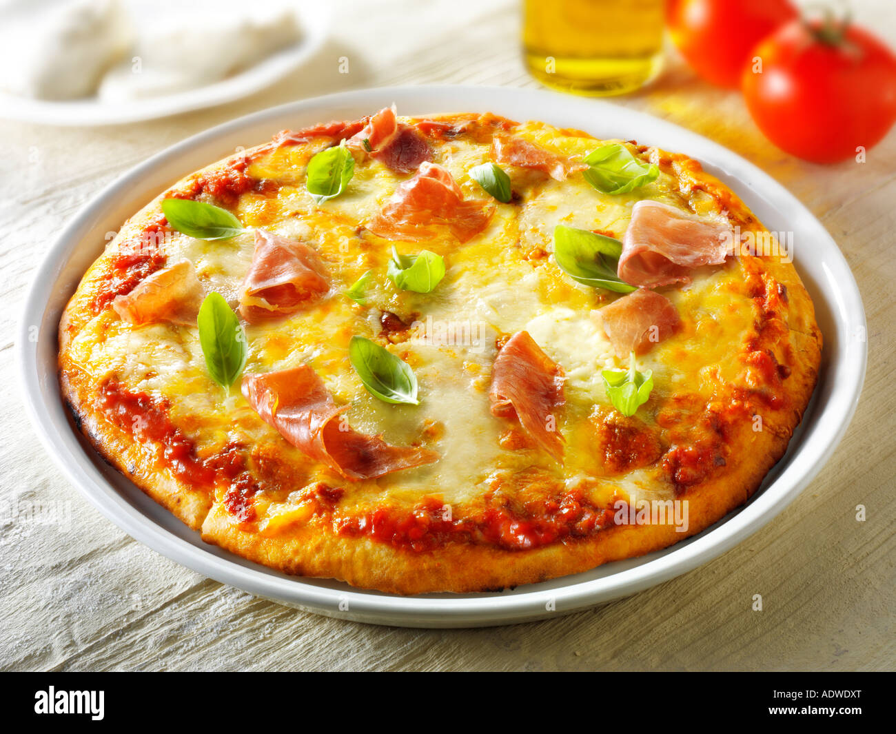 Pizza topped with 3 cheeses Parma ham basil - Stock Image