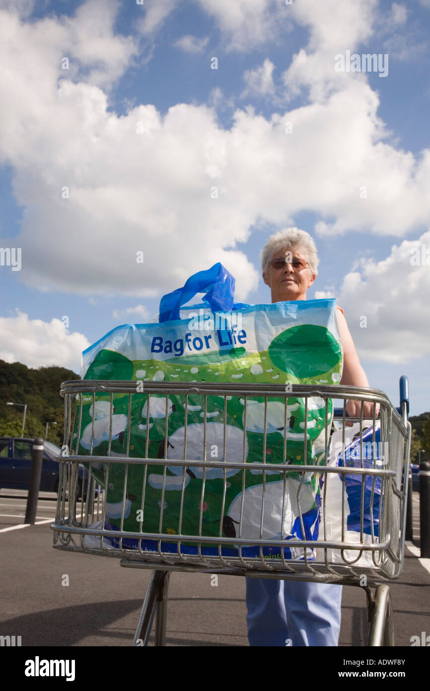 Senior woman pushing a shopping trolley carrying a plastic 'bag for life' from Tesco supermarket. UK Britain - Stock Image
