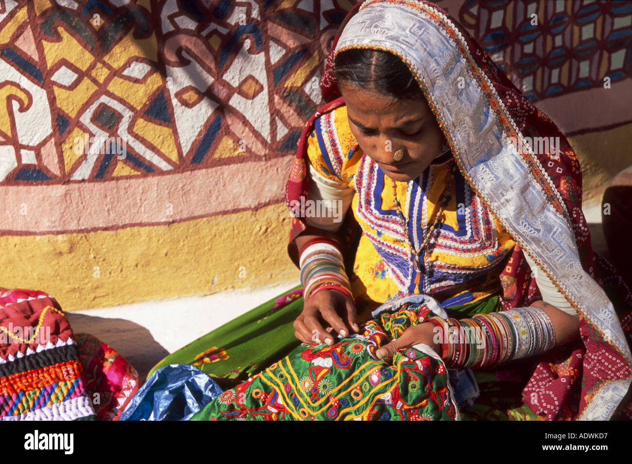 Tribal woman doing embroidery outside her home in the village of Ludia near Bhuj Kutch region of Gujarat India - Stock Image