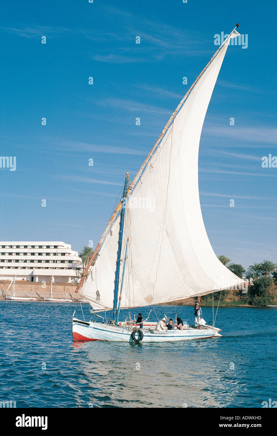 Felucca or sailing boat passing the Sheraton Luxor Hotel on the River Nile Egypt north Africa - Stock Image