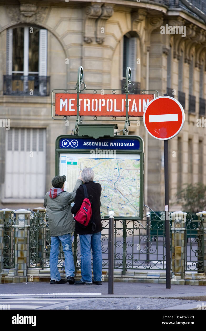 Tourists on foot study Metropolitain subway map for the Paris Metro in Rue du Bac Left Bank Paris France - Stock Image