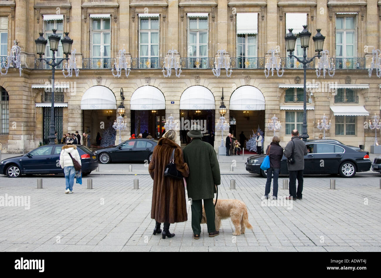 Couple with dog gaze at Ritz Hotel in Place Vendome Central Paris France - Stock Image