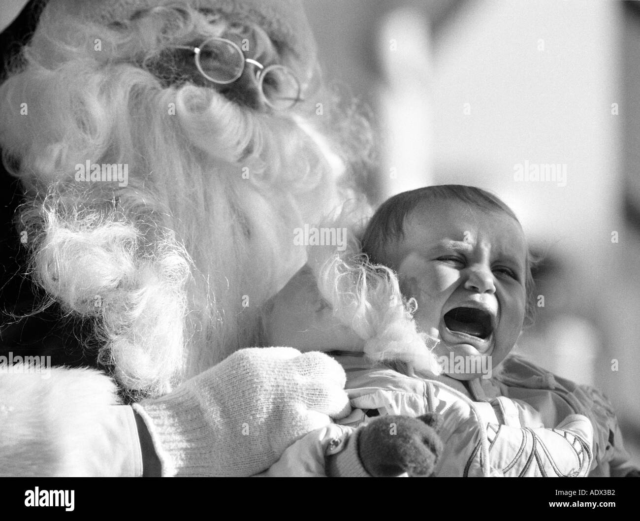 Fake santa claus holding crying baby scared child humor st nick saint nick christmas party - Stock Image