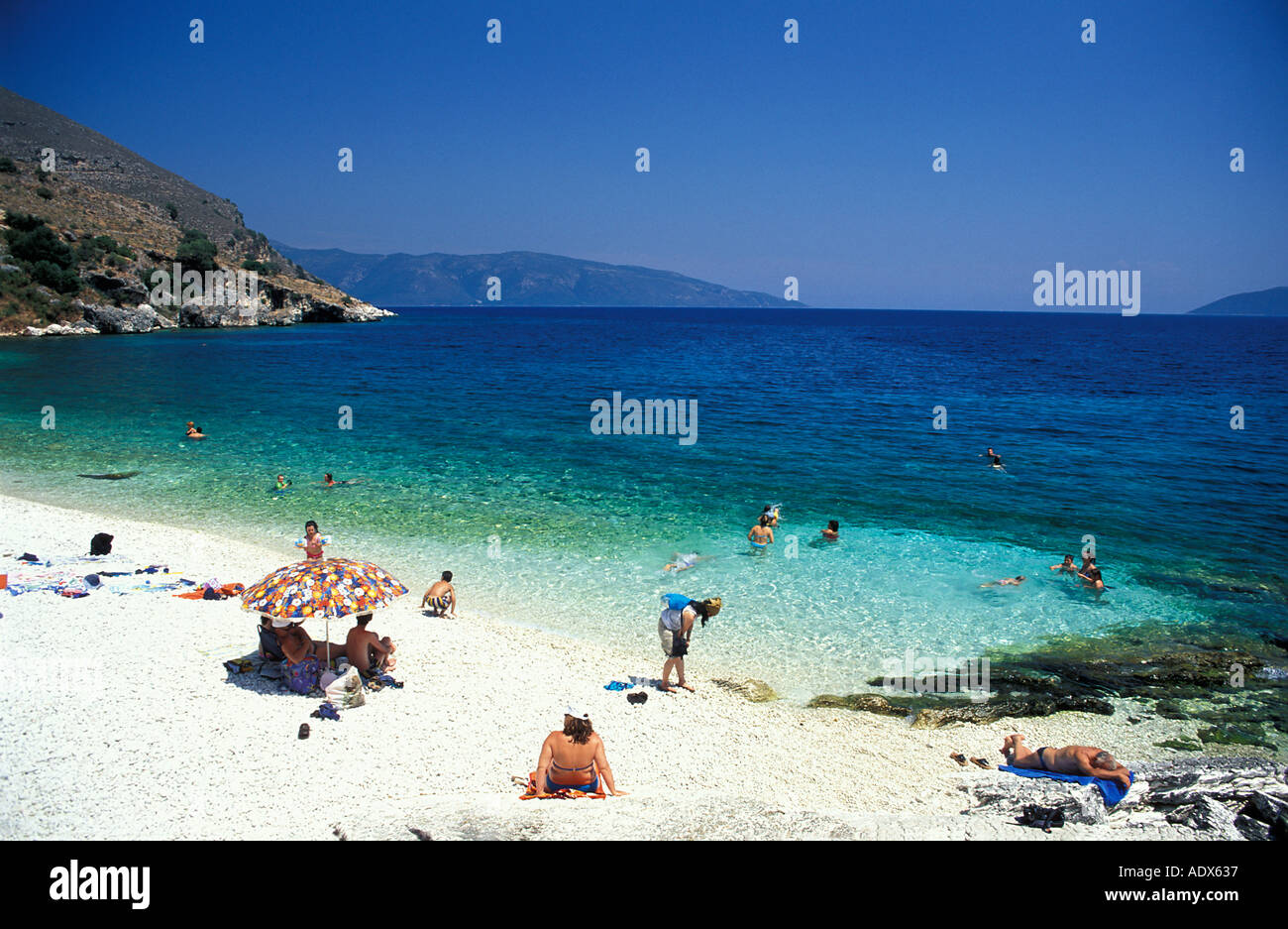 Relaxing on the beach at Aghia Efimia a picturesque seaside town Kefalonia Greece Mediterranean Sea - Stock Image