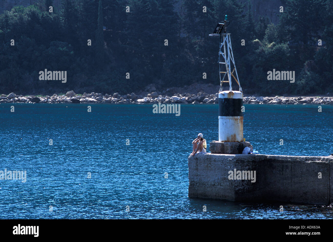 Woman using her cellular mobile telephone whilst fishing at the end of the harbour arm Poros Kefalonia - Stock Image