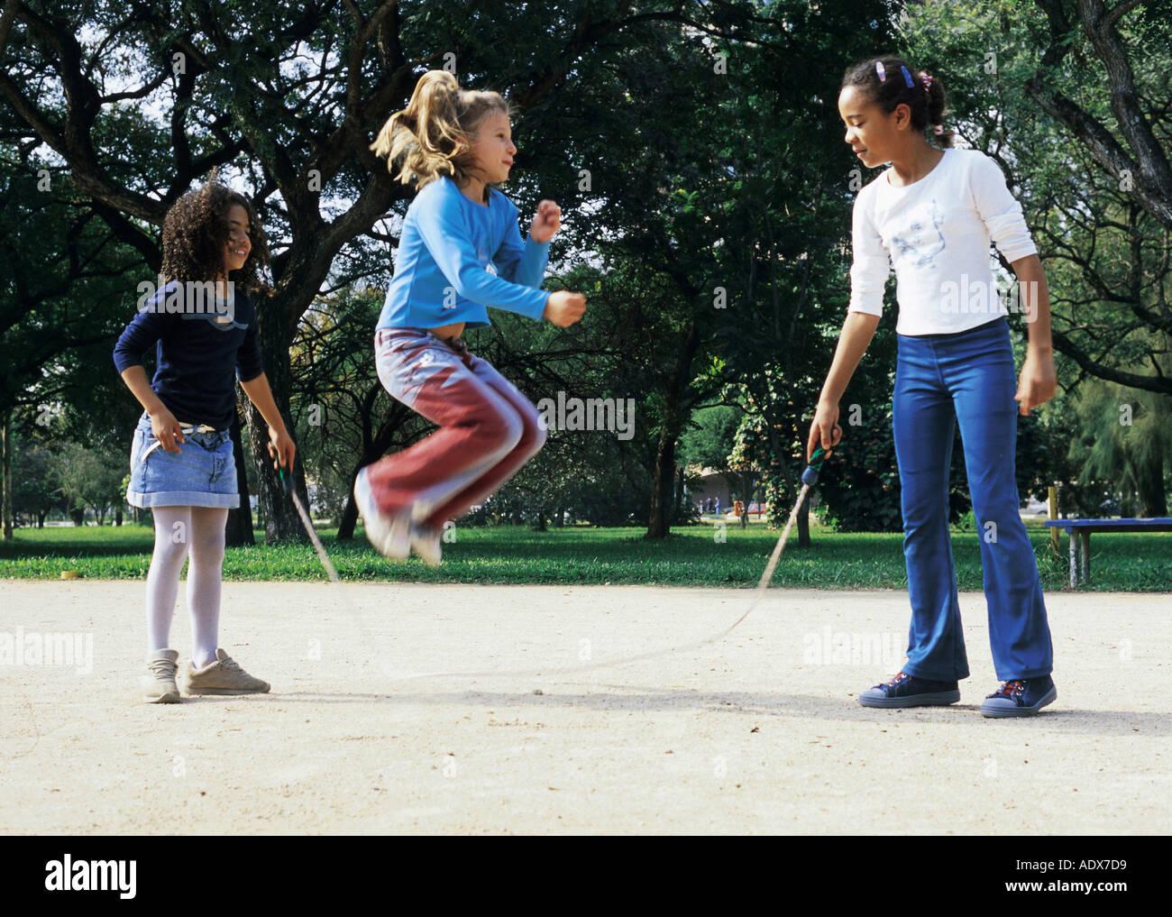 Children kids girls children jumping rope three standing ...