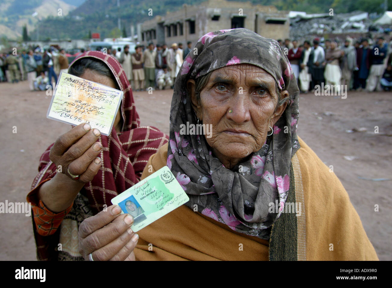 Women showing their ID cards hoping to get also food during a distribution in Hatian - Stock Image