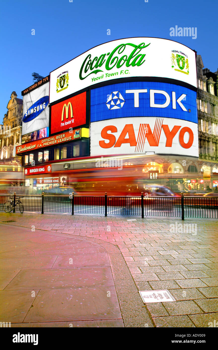 Piccadilly Circus in London with its neon digital signs in the early evening. - Stock Image