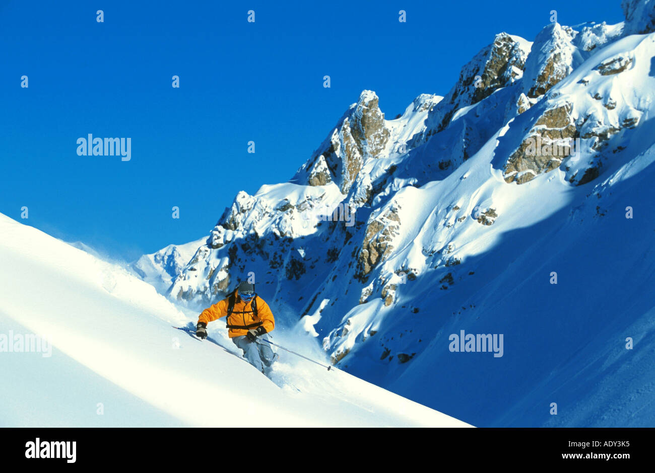male skier, downhill skiing in deep snow, off-piste, France - Stock Image