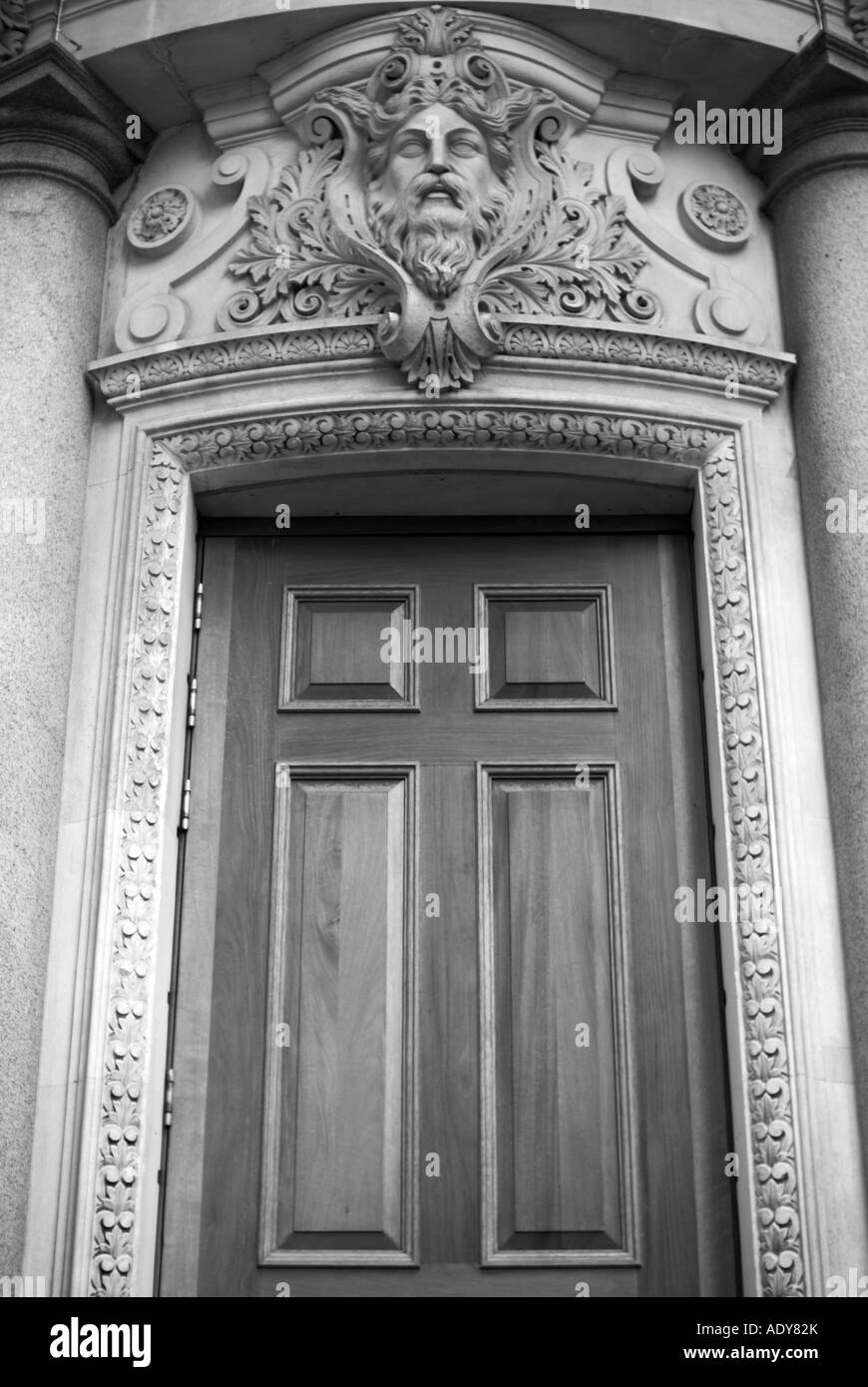 Door in Whitehall with carved stone head. - Stock Image