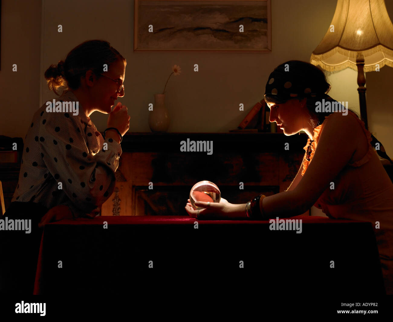 Fortune teller and client looking into crystal ball - Stock Image