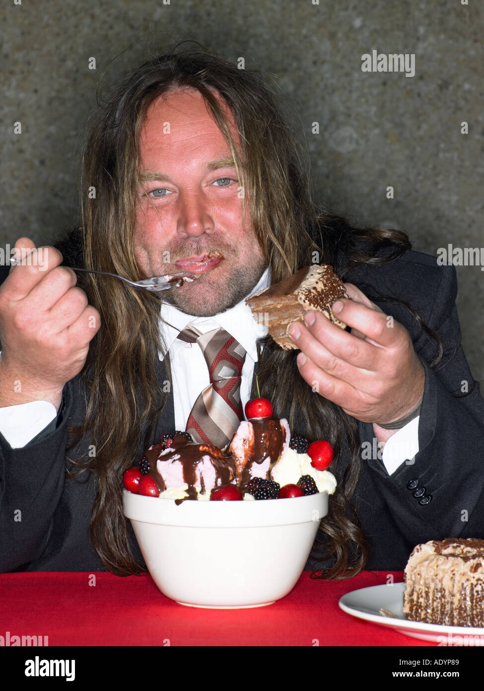 Long haired fat man eating stuffing himself with ice cream - Stock Image