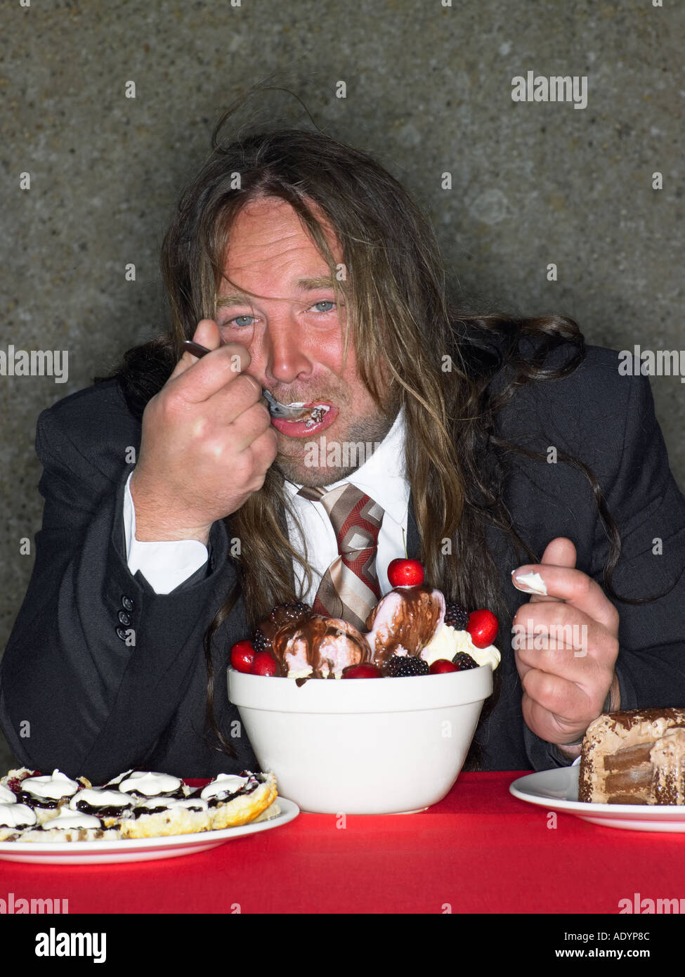 Long haired fat man eating stuffing himself with cake and ice cream - Stock Image